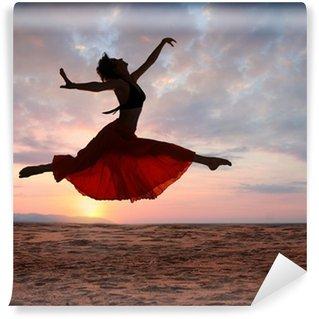 Papier Peint Vinyle Femme sautant au coucher du soleil