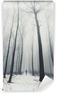 Papier Peint Vinyle L'homme dans la forêt avec de grands arbres en hiver