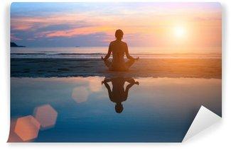 Papier Peint Lavable Silhouette jeune femme pratiquant le yoga sur la plage au coucher du soleil.