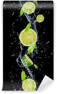 Papier Peint Vinyle Limes dans les projections d'eau, isolé sur fond noir