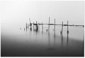 En lang eksponering af en ødelagt pier i midten af havet. Behandlet i B & W. Plakat
