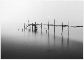 Plakat En lang eksponering av en ødelagt pir i midten av havet. Behandlet i B & W.