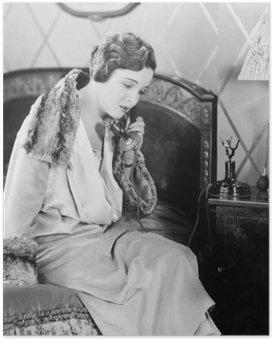 Ung kvinde sidder på sin seng i sengeværelset og taler i telefon Plakat