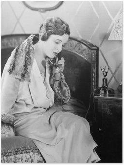 Plakát HD Mladá žena sedí na posteli v ložnici, mluví po telefonu