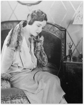 Plakát Mladá žena sedí na posteli v ložnici, mluví po telefonu