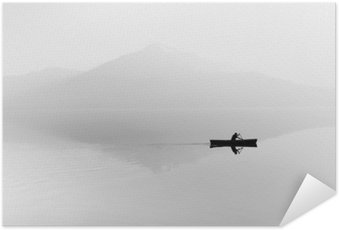 Poster Dimma över sjön. Siluett av bergen i bakgrunden. Mannen flyter i en båt med en paddel. Svartvitt