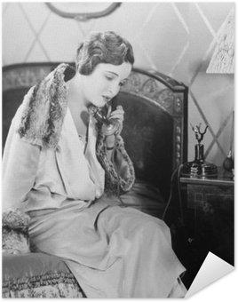 Póster HD Mujer joven sentada en su cama en la sala de la cama, hablando por teléfono
