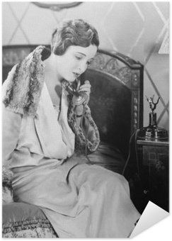 Poster HD Young woman sitting on her bed in the bed room, speaking on the telephone