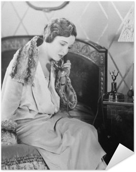 Poster Young woman sitting on her bed in the bed room, speaking on the telephone