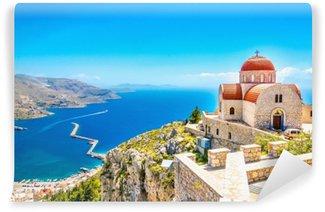 Samolepicí Fototapeta Vzdálený kostel s červenou střechou na útesu, řecko