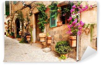 Selbstklebende Fototapete Romantische Gasse mit Blumen und Grün