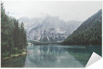 Selbstklebendes Poster Wildsee mit grünem Wasser und Berge mit trees__