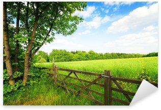 Sticker Pixerstick Clôture dans le champ vert sous un ciel bleu