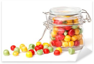 Colorful candies in glass jar. Isolated on white Sticker - Pixerstick
