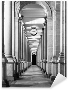 Sticker - Pixerstick Long colonnafe corridor with columns and clock hanging from ceiling. Cloister perspective. . Black and white image.