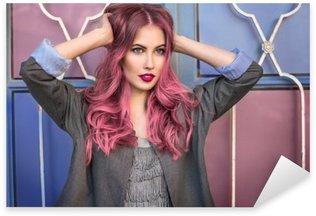 Pixerstick Sticker Mooie hipster mannequin met krullend roze haar poseren voor de kleurrijke muur