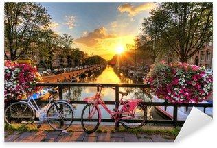 Pixerstick Sticker Mooie zonsopgang over Amsterdam, Nederland, met bloemen en fietsen op de brug in het voorjaar