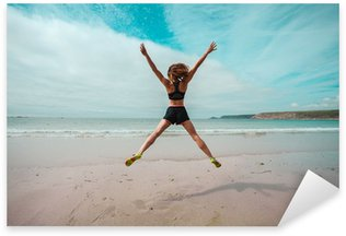 Young woman doing star jumps on the beach Sticker - Pixerstick