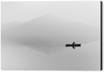 Tableau Alu-Dibond Brouillard sur le lac. Silhouette de montagnes en arrière-plan. L'homme flotte dans un bateau avec une pagaie. Noir et blanc
