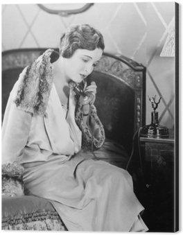 Tableau Alu-Dibond Jeune femme assise sur son lit dans la chambre à coucher, en parlant au téléphone