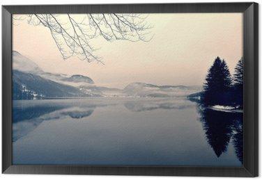 Tableau en Cadre Paysage d'hiver enneigé sur le lac en noir et blanc. image monochrome filtrée rétro, style vintage avec un accent doux, filtre rouge et un peu de bruit; notion nostalgique de l'hiver. Lac Bohinj, Slovénie.