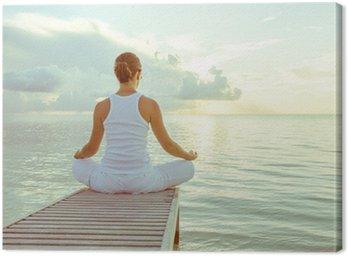 Tableau sur Toile Caucasien femme pratiquant le yoga au bord de la mer