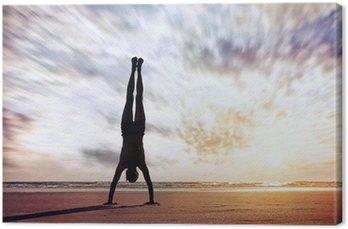 Tableau sur Toile Équilibre sur les mains près de l'océan
