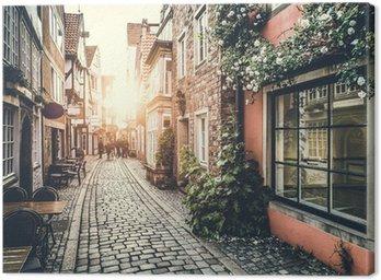 Tableau sur Toile Rue historique en Europe sous un coucher de soleil