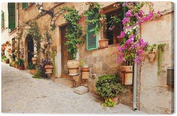 Tableau sur Toile Rue romantique avec des fleurs et de la verdure