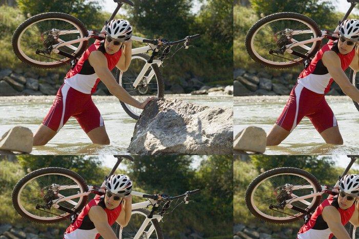 Tapeta Pixerstick Muž nesoucí na kole přes potok. -