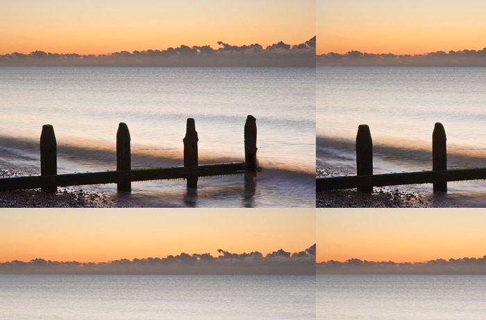 Tapeta Pixerstick Staré vlnolamy na pláži poslední obrany při východu slunce proti přílivu - Voda