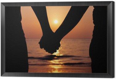 Tavla i Ram Silhouettes par håller varandra i handen på solnedgången.