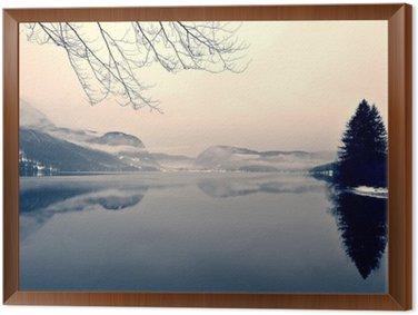 Tavla i Ram Snöiga vinterlandskapet på sjön i svart och vitt. Svartvit bild filtreras i retro, vintage-stil med mjukt fokus, rött filter och vissa buller; nostalgiska begreppet vinter. Lake Bohinj, Slovenien.