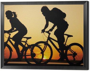 Tavla i Ram Unga par ridning cyklar vid solnedgången.