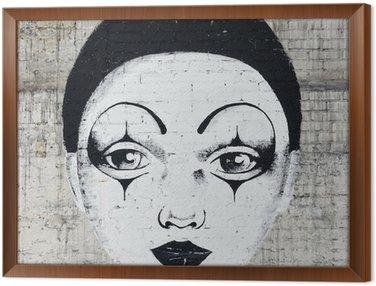 Tavla i Ram White inför clown graffiti på en brickwall