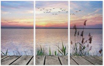 Triptyk Lake av färgglada moln