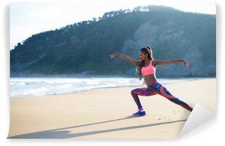 Tvättbar Fototapet Fitness kvinna sträcker benen och öva dans poserar på stranden. Svart kvinnliga idrottare tränar utomhus mot havet.