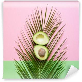 Tvättbar Fototapet Mogen avokado på palmblad på en färgad bakgrund. minimal koncept