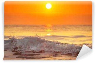 Tvättbar Fototapet Soluppgång och lysande vågor i havet