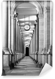 Pitkä colonnafe käytävällä sarakkeineen ja kello roikkuu katosta. luostarin näkökulma. . mustavalkoinen kuva. Vinyyli Valokuvatapetti
