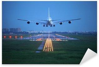 Vinilo Pixerstick Avión de pasajeros volar a lo largo de la pista de despegue del aeropuerto