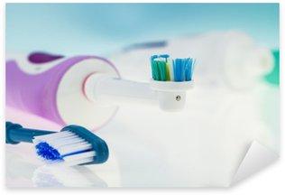 Vinilo Pixerstick Cepillo de dientes eléctrico y clásico en la superficie reflectante y el fondo azul claro.