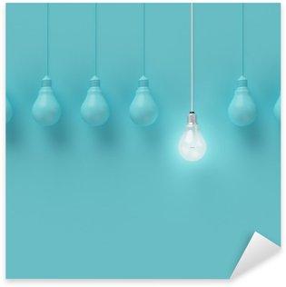 Vinilo Pixerstick Colgar las bombillas con una brillante idea diferente sobre fondo azul claro, la idea Mínimo concepto, en plano, la parte superior