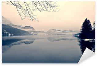 Vinilo Pixerstick Paisaje de invierno cubierto de nieve en el lago en blanco y negro. imagen monocroma filtrada en retro, estilo de la vendimia con enfoque suave, filtro rojo y el ruido; concepto nostálgica de invierno. Lago Bohinj, Eslovenia.