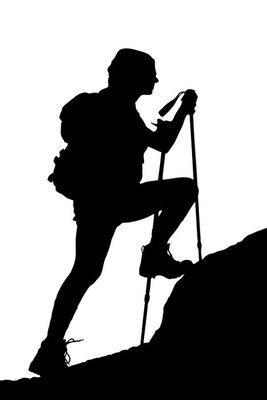 A silhouette of a female climbing a cliff