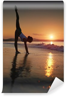 A woman doing a yoga workout at the beach during a sunrise