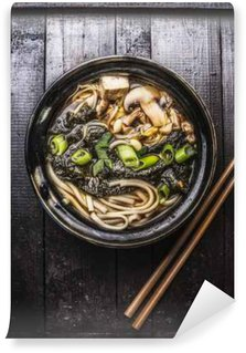 Wall Mural - Vinyl Asian ramen soup with noodles, tofu and nori seaweed in bowl with Chopsticks on dark wooden background.