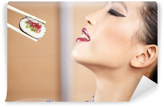 Wall Mural - Vinyl beautiful asian woman eating sushi with chopsticks