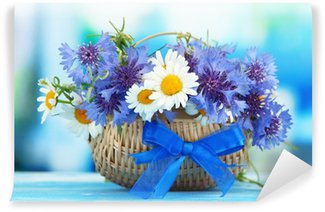 Beautiful bouquet of cornflowers and chamomiles in basket