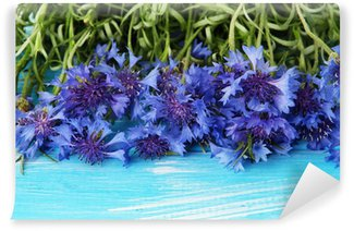 Beautiful bouquet of cornflowers on blue wooden background